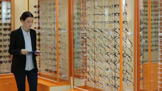 Optician checking showcase with glasses in store