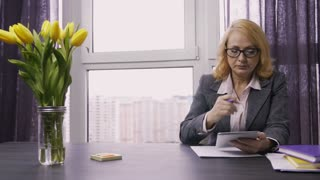 Pensive senior adult woman sitting at desk in office, holding pen in hands and working on tablet pc. Blond hair business female thinking and brainstorming with touchpad in hands. Dolly shot