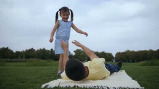 Playful father lying on picnic blanket lifting up his cute laughing daughter in summer park. Excited full of energy girl making plane holding hands to the side while dad lifting and keeping her above