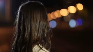 Playful smiling woman flirting on street at night