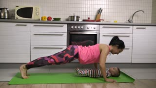 Playful young beautiful mother having fun with child making sport at home in the kitchen. Cute baby lying on yoga mat, woman doing push-ups and kissing her sweet infant child. Slow motion. Dolly shot
