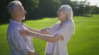 Portrait of attractive senior couple with gray hair laughing together on green lawn. Happy funny aged husband and wife enjoying outdoors and laughing out loud. Positive moment of retired seniors.