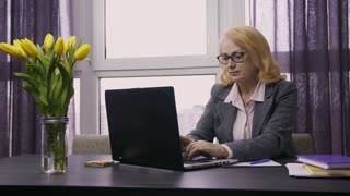 Portrait of attractive senior female worker sitting at office desk, typing and browsing pages on laptop. Businesswoman in spectacles in formal jacket working at the table on laptop pc. Dolly shot