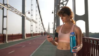 Portrait of attractive senior redhead runner on city bridge using mobile phone. Athletic female jogging at sunrise taking a break to create running route on smartphone application.