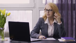 Portrait of beautiful blond hair senior adult woman talking on mobile phone and using laptop pc at work. Smiling businesswoman in formal jacket and eyeglasses taking notes, using smartphone and laptop