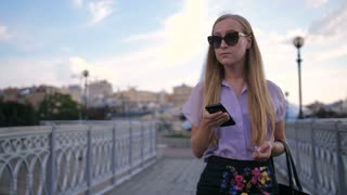 Portrait of beautiful blonde business lady in cat eye sunglasses walking alone on urban city bridge holding mobile phone. Corporate woman smiling while scrolling social media and texting on smartphone