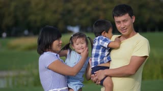 Portrait of cheerful asian family with two cute little kids waving hands together and smiling while standing in park. Positive multinational parents holding preschool siblings and greeting outdoors.