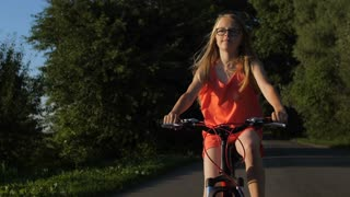 Portrait of cute blonde teenage girl riding bicycle and enjoying nature views in countryside at sunset. Positive teenager cycling on a trip on rural road. Steadicam shot