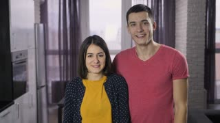 Portrait of delighted young couple standing in the house and shaking keys to new home at camera. Cheerful excited couple holding keys and dancing. Slow motion. Keys with wooden house shaped key ring.