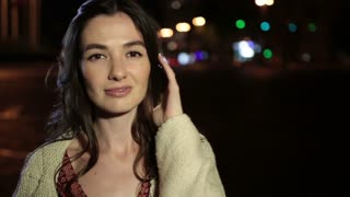 Portrait of elegant woman posing outdoors at night