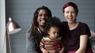 Portrait of happy diverse family with son at home