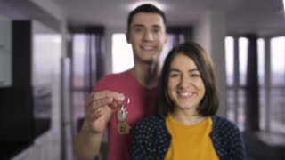Portrait of happy married couple standing indoors and shaking keys to new house. Male hand holding keys and offering it to the camera. Slow motion. Keys with wooden house shaped key ring.