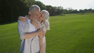 Portrait of lovely senior woman with white hair hugging her husband with beard from behind and whispering to his ear. Affection and love at old age. Sweet elderly couple enjoying. 180 degree shot