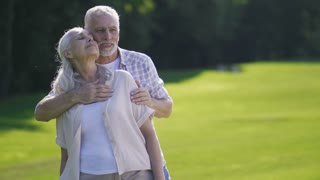 Portrait of passionate senior couple standing on green lawn in summer. Loving husband embracing beautiful wife with gray hair, touching and kissing her. Affectionate seniors in love during a date