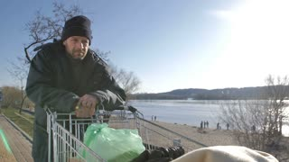 Portrait of poor desparate mature homeless man walking near the river pushing shopping cart on a cold autumn day. Bearded male in hat and warm jacket looking for shelter. Steadicam shot.