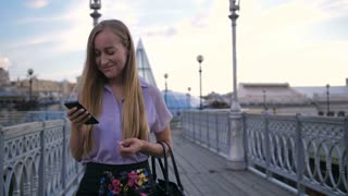 Portrait of young attractive blonde businesswoman walking on city bridge with smartphone in hand. Female xecutive texting and scrolling newsfeed on social media during a stroll at lunch break