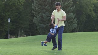 Positive asian father playing with his cute little son and spinning him while standing on green grass in public park. Cheerful dad whirling his giggling boy while family having fun in nature.