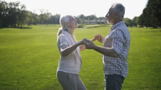 Positive attractive mature couple of married seniors dancing and singing together on green lawn in countryside. Happy elderly wife and husband with grey hair enjoying life and retirement outdoors