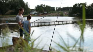 Positive dad and son with rod angling at pond