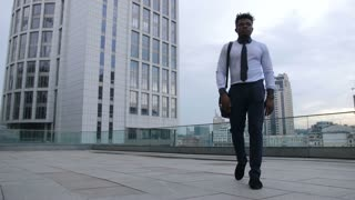 Positive dark-skinned businessman walking along the street outside office building and making afrohouse dance moves while nobody see him. Serious black entrepreneur in nice mood dancing outdoors.
