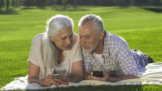Positive happy senior couple lying on blanket on green lawn during travel and posting vacation photos on social media using mobile phones. Smiling retired elderly wife and husband smiling and laughing