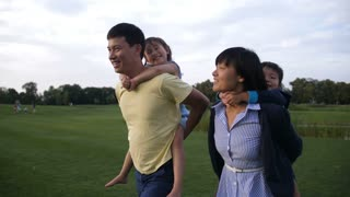 Positive multi ethnic parents giving cute laughing little siblings piggyback ride while having fun in summer park. Smiling asian mother and father piggybacking their joyful preschool children outdoors