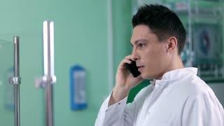 Positive pharmacist calling on phone in drugstore