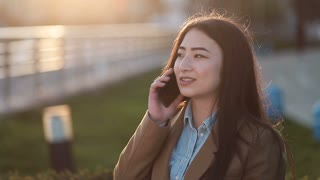 Positive young asian woman talking on mobile phone