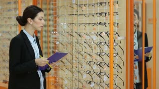 Pretty female optician revising glasses in optics