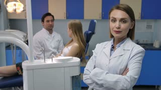 Pretty mid adult female dentist standing and smiling to camera with arms crossed in lab coat. Male dental doctor's assistant talking to female patient in dental chair at background at dental office