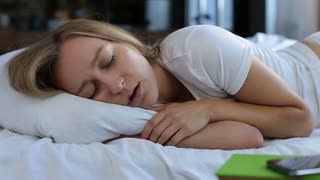 Pretty young woman snoring in bed