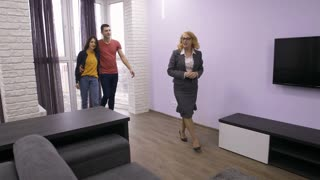 Professional female realtor showing contemporary style apartment to young adults couple. Husband and wife listening to senior real-estate agent, looking at furniture, sitting on sofa. Steadicam shot.