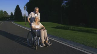 Real love. Beautiful senior couple enjoying sunset in countryside. Man pushing paralyzed wife in wheelchair while they walk and woman raising arms like flying. Positive happy retirement. Steadicam