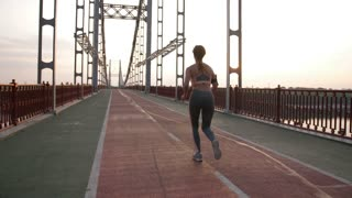 Rear view of beautiful redhead senior female runner running during morning workout on city bridge. Active woman jogging outdoors at sunrise. Steadicam stabilized shot