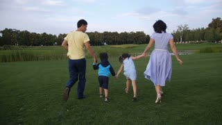 Rear view of carefree positive asian family with two preschool kids holding hands and running on green park lawn while relaxing together in nature. Happy parents and joyful children running outdoors.