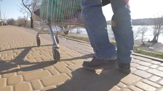 Rear view of homeless man's legs walking with shopping cart down the road on river bank. Beggar male pushing cart with his belongings. Homelessness and social issues concept. Steadicam shot.