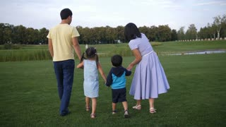 Rear view of positive asian family holding hands and walking in nature while enjoying weekend in public park. Happy relaxed family with two little siblings spending leisure in nature on summer day.