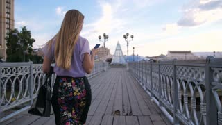 Rear view of stylish blonde businesswoman with long hair walking on urban city bridge with bag and cellphone in hand. Executive female during lunch break texting on smartphone while walking.