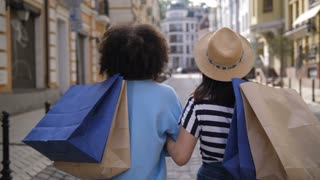 Rear view of two young girls with shopping bags walking along city sreet. Mixed race and asian shopaholic women looking at camera and smiling happily after successful shopping day in shopping mall