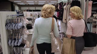 Rear view of women walking in clothing store