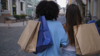 Rear view shot of two female friends walking with shopping bags on shoulders in city center. Mixed race and caucasian teen women turning to camera and smiling with happiness after good shopping day