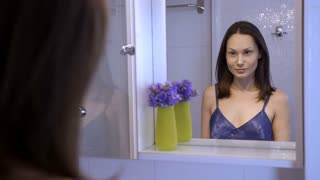 Reflection of pretty brunette woman looking at herself in the mirror. Young female with a confident look admiring her skin and hair. Body positive girl satisfied with her face and body.