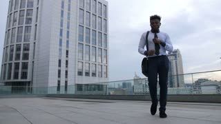 Relaxed joyful african american businessman taking break and giving himself minutes of joy while dancing afrobeat style outside office building. Successful executive in afrohouse dance on city street.