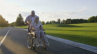 Retired senior couple having fun in summer countryside. Bearded aged husband running pushing disabled wife on wheelchair. Beautiful paralyzed woman with gray hair enjoying life and laughing. Steadicam