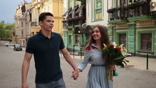 Romantic couple in love strolling down city street