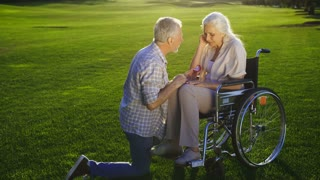 Romantic moment of senior couple in love. Handsome elderly bearded man standing on knee and proposing his gray haired mature girlfriend to marry with engagement ring. Woman accepting marriage proposal