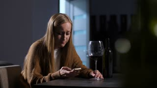 Sad adult wife in tears with glass of wine text messaging on cellphone while sitting alone in domestic room at night. Worried crying woman typing message on smart phone after breakdown with husband.