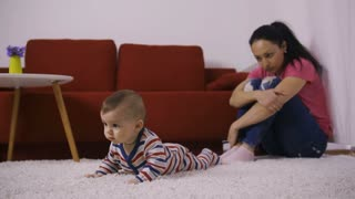 Sad attractive latin mother sitting near the wall with arms around her knees, watching her joyful cute baby boy crawling on the carpet. Young mother with absent unhappy look. Dolly shot
