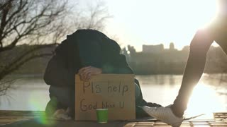 Sad broken beggar sitting on the street with his head down, asking for help at sunset on the river bank in city. Abandoned homeless male holding cardboard sign and sleeping. Dolly shot