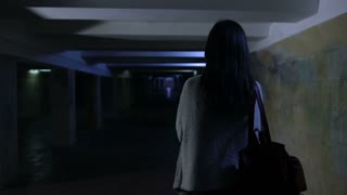 Scared woman screaming in dark underpass at night
